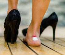 High heels hurts very often, feet with white little patch on ankle, one feet on - stock photo