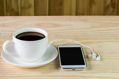 smart phone and coffee on wooden table - stock photo