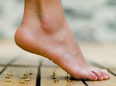 Feet almost walking on tacks, wooden floor - stock photo