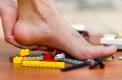 A feet get hurt with some legos on the floor. Various colors, red, white, yellow Stock Photos