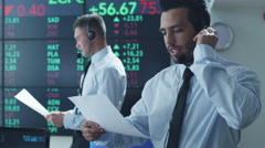 Hispanic Ethnicity Stockbroker is Actively Talking using Headset at Stock Exchan Stock Footage
