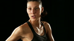 Young athletic woman wearing sporstwear is warming up isolated on black Stock Footage