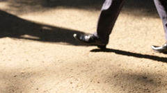 Man walking on sidewalk - shadow of body - closeup foot Stock Footage