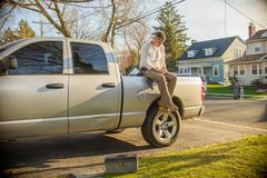 Handyman using smartphone on rear of truck Stock Photos