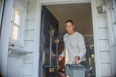 Handyman leaving house Stock Photos