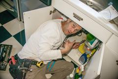 Handyman fixing kitchen sink pipe Stock Photos