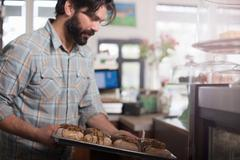 Bakery owner placing tray of vegan, allergy-friendly doughnuts into display case - stock photo