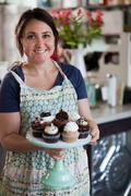 Bakery owner carrying tray of allergy-friendly cupcakes Stock Photos