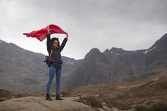 Woman holding red flag in mountains, Fairy Pools, Isle of Skye, Hebrides, Stock Photos