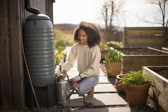 Mid adult woman filling watering can from water butt - stock photo