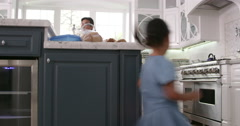 Parents Prepare Food As Children Play In Kitchen On R3D Stock Footage