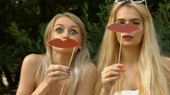 Teenage girls friends making funny faces to the camera with moustache and pro - stock footage
