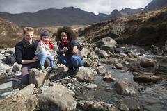 Family by stream, Fairy Pools, Isle of Skye, Hebrides, Scotland Stock Photos