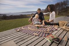 Boy and parents playing with toy train on wooden decking Stock Photos