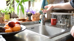 Man washes dishes and water is sprayed around Stock Footage