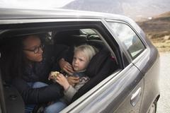 Mother adjusting son's seatbelt in car Stock Photos