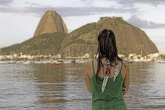 Mid adult woman looking out towards Sugarloaf mountain, Botafogo bay, Rio de - stock photo