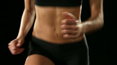 Young athletic woman wearing sporstwear is exercising isolated on black Stock Footage