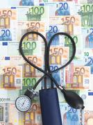Blood pressure gauge on top of euro currency notes, tubes twisted into heart Kuvituskuvat