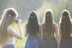 Rear view of teenage girl photographing friends wearing daisy chain headdresses - stock photo