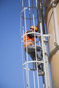 Worker climbing smoke stack ladder Stock Photos