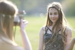 Teenage girl photographing best friend using instant camera in park - stock photo