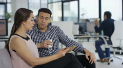 4K Business man & woman in modern office, looking at tablet & discussing ideas Stock Footage