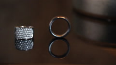Wedding ring rolling into other wedding ring. - stock footage