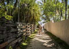 Young couple holding hands on path to Lanikai Beach, Oahu, Hawaii, USA - stock photo