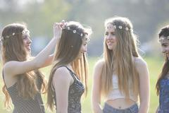 Teenage girls putting on and wearing daisy chain headdresses in park - stock photo