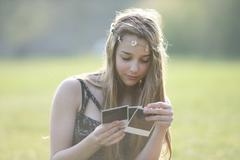 Teenage girl wearing daisy chain headdresses looking at instant photographs in - stock photo