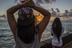 Two young women watching sunrise, Kaaawa beach, Oahu, Hawaii, USA - stock photo