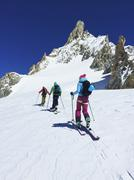 Rear view of three adult skiers moving up Mont Blanc massif, Graian Alps, France Stock Photos