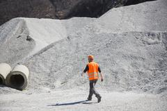 Quarry worker walking through gravel mounds at quarry - stock photo