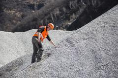 Quarry worker measuring on gravel mound at quarry Stock Photos
