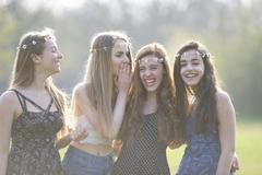 Four teenage girls wearing daisy chain headdresses giggling in park - stock photo