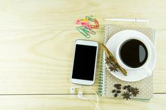 Smart phone, coffee,glasses and book blank with white pen on wood table backg Stock Photos