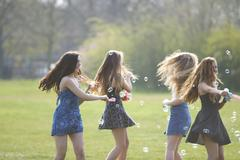 Four teenage girls spinning bubbles with bubble wand in park - stock photo