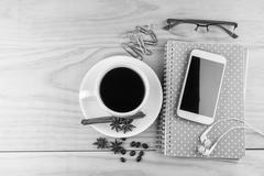Smart phone, coffee,glasses and note book on wood table background. Stock Photos