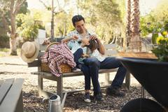 Mid adult man with hand on daughters forehead on community garden bench Stock Photos