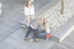 Businesswomen hugging on hotel terrace Stock Photos