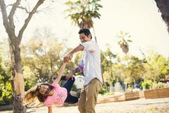 Mid adult man swinging daughter in community garden Stock Photos