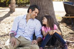 Girl and father leaning against tree in community garden - stock photo
