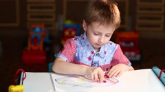 Boy Paints the Car With Crayons Sitting at Table Stock Footage