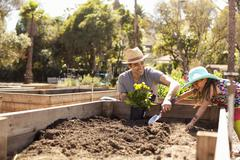 Mid adult man and daughter digging flower bed in community garden Stock Photos