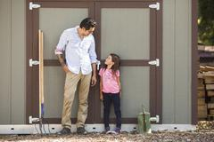 Girl looking at father in front of community garden shed Stock Photos