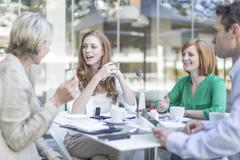 Businesswomen and man meeting at coffee break on hotel terrace Stock Photos