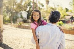Portrait of girl in community garden carried by father Stock Photos