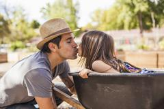 Mid adult man in community garden kissing daughter in wheelbarrow Stock Photos