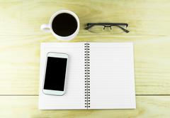 Smart phone, coffee,glasses and book blank on wood table background. - stock photo